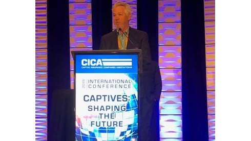 Gary Bowers presenting on stage behind podium at CICA 2019 conference