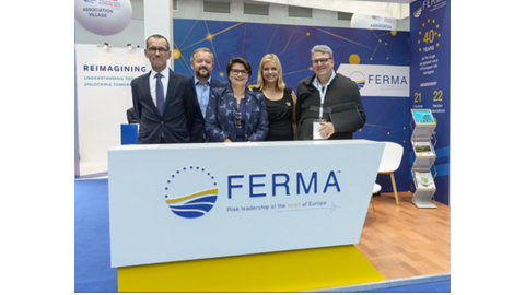 Group of people standing behind FERMA counter at trade show