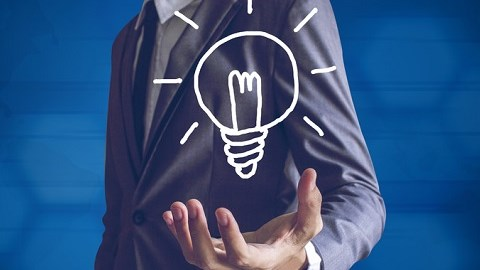 Businessman holding a drawn lightbulb with illumination lines